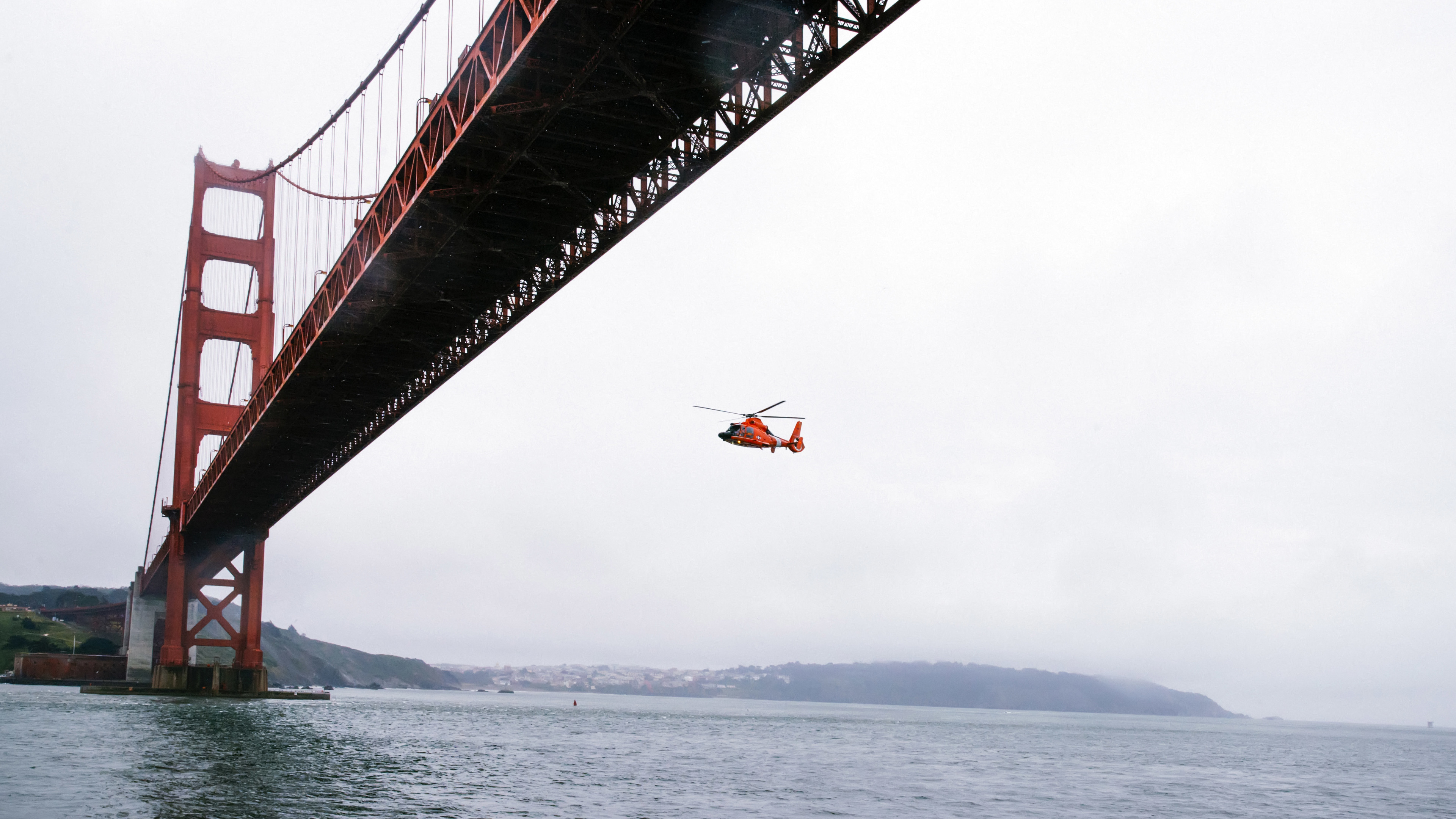 rescue helicopter flying under golden gate bridge 1538069323 - Rescue Helicopter Flying Under Golden Gate Bridge - world wallpapers, san francisco wallpapers, hd-wallpapers, golden gate bridge wallpapers, bridge wallpapers, 4k-wallpapers
