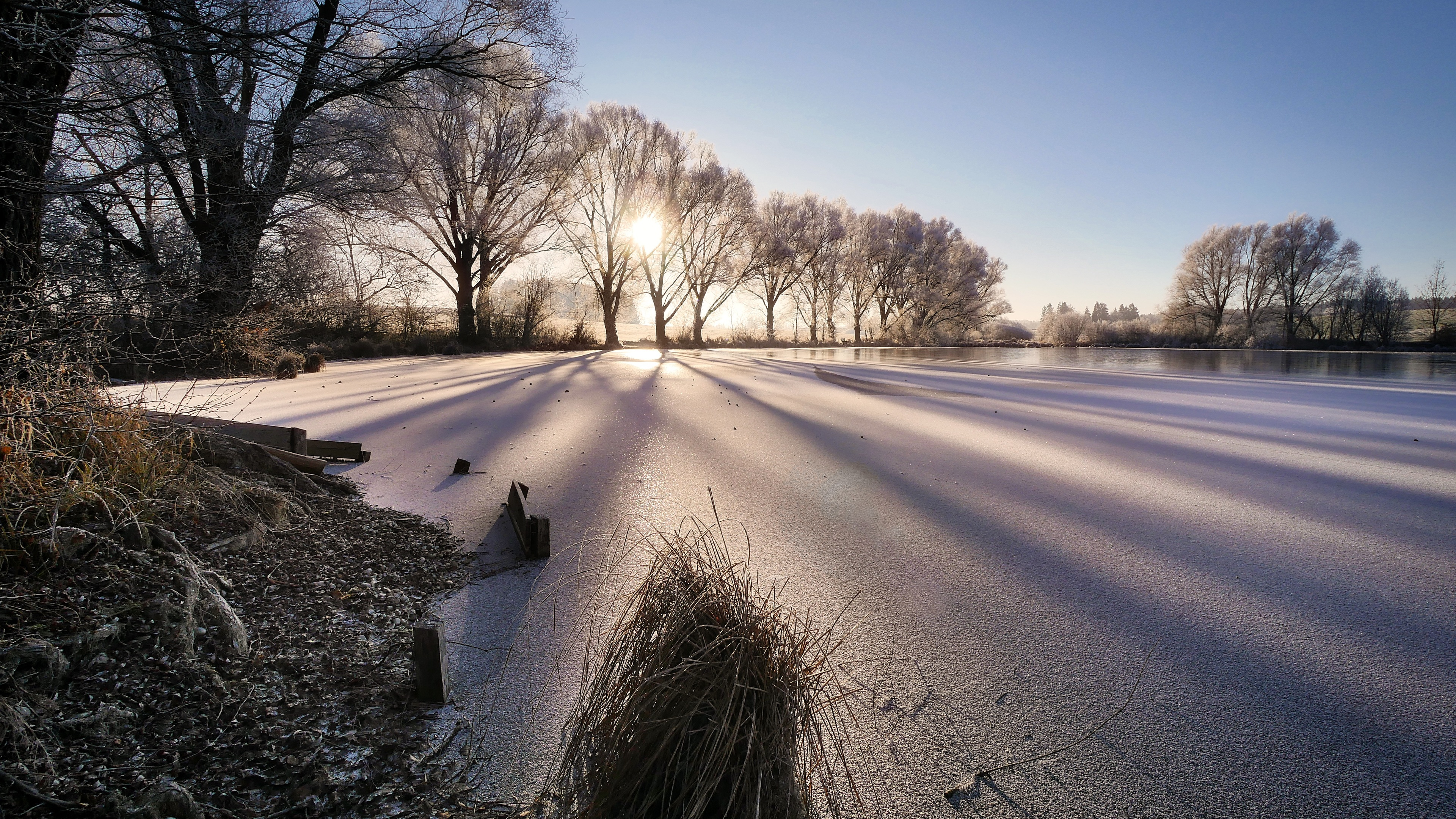cold wintry frozen lake sunbeam trees 4k 1540134127 - Cold Wintry Frozen Lake Sunbeam Trees 4k - winter wallpapers, trees wallpapers, sunbeam wallpapers, lake wallpapers, hd-wallpapers, frozen wallpapers, cold wallpapers, 5k wallpapers, 4k-wallpapers