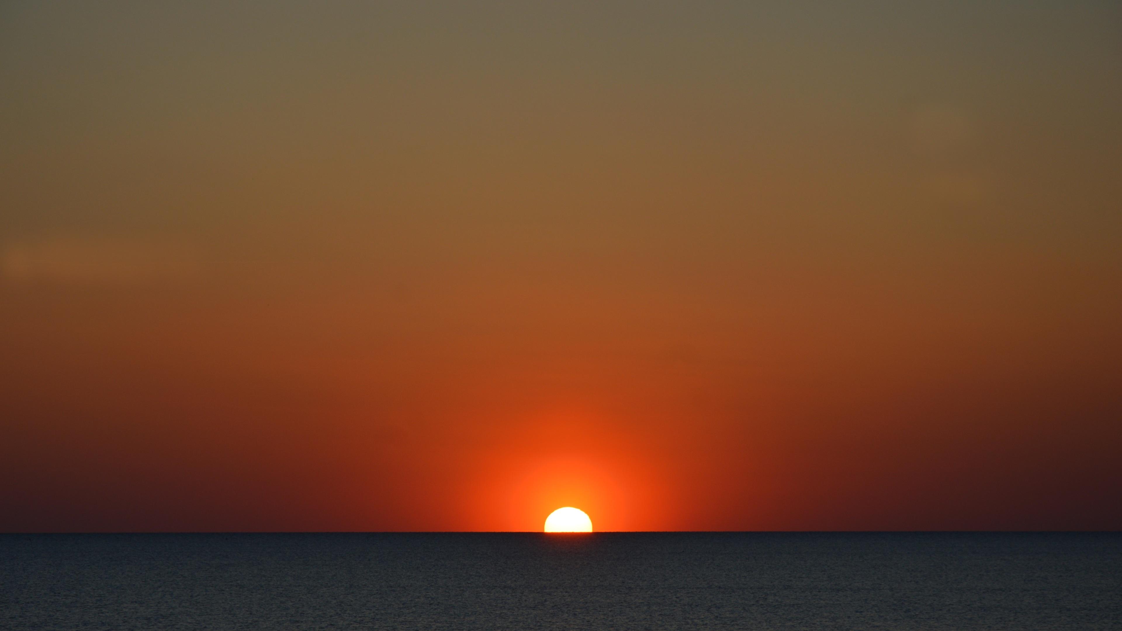 sun setting in body of water 4k 1540136316 - Sun Setting In Body Of Water 4k - sunset wallpapers, nature wallpapers, hd-wallpapers, 5k wallpapers, 4k-wallpapers