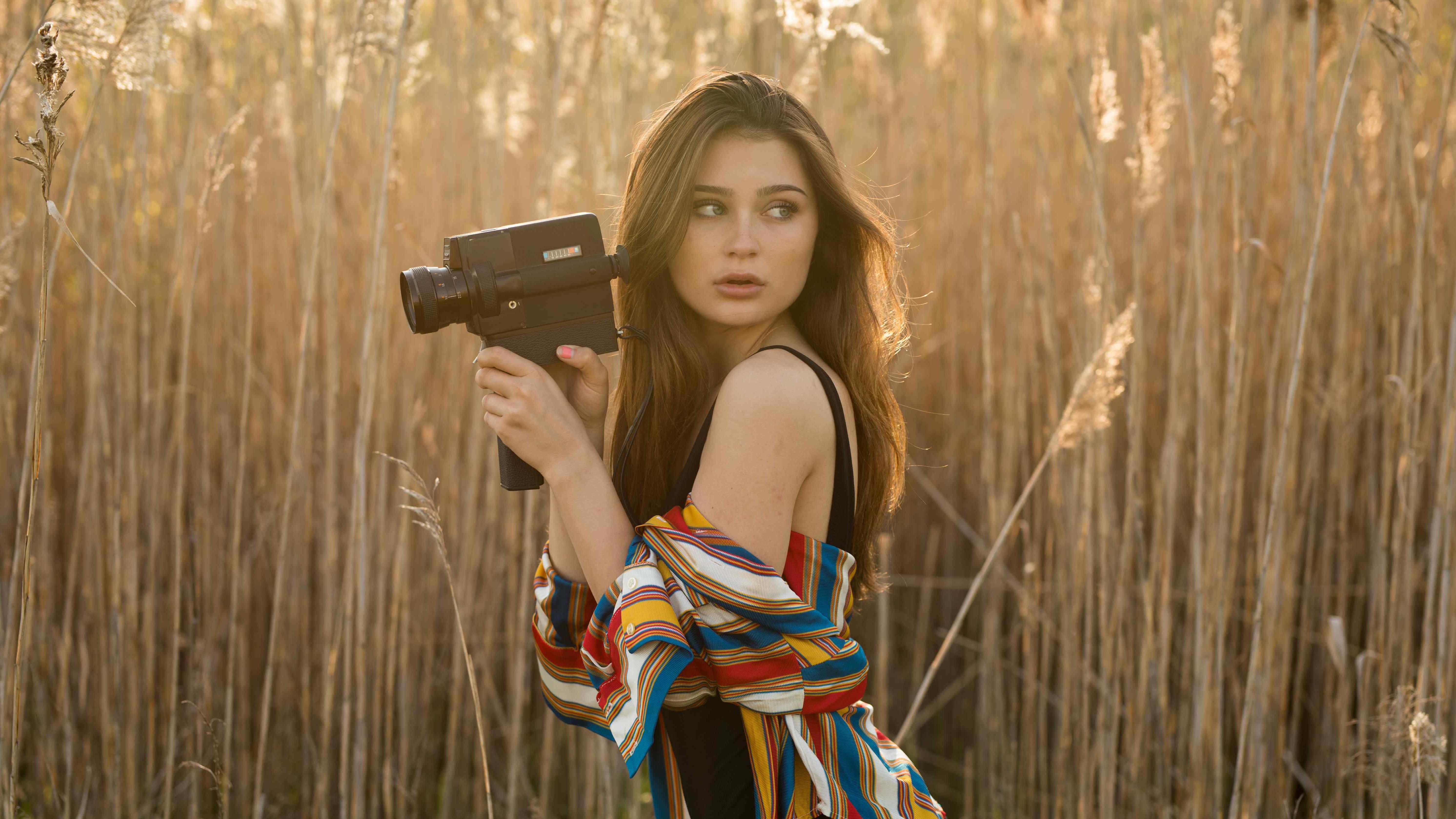 brunette girl in field with camera 1575664956 - Brunette Girl In Field With Camera -